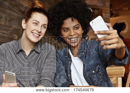 Stylish African-american Girl With Afro Haircut Holding Mobile, Taking Selfie With Her Charming Beau