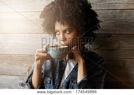 Indoor Shot Of Beautiful African-american Woman With Afro Hairstyle Holding Big Mug, Having Fresh Ca