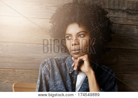 Close up portrait of attractive good-looking young Africa female with curly haircut resting chin on her hand having wistful reflective expression posing indoors dressed in trendy jeans jacket