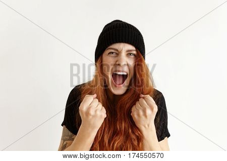 Portrait Of Mad And Furious Young Redhead Woman In Hipster Hat Expressing Rage And Anger, Clenching