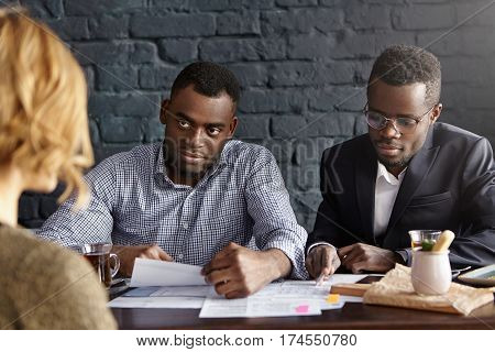 Attractive Dark-skinned Hr Manager Reading Curriculum Vitae In His Hands While Conducting Job Interv