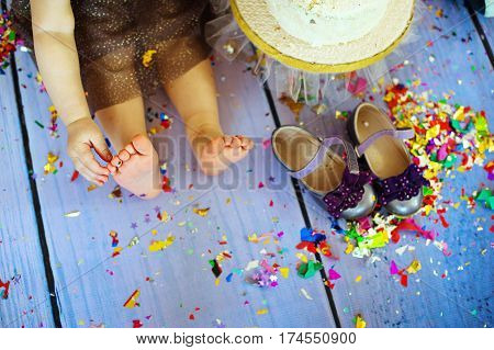 Top view on child's feet on the snow ground with confetti. Holidays, winter and Christmas. Outdoor. Family celebrating.