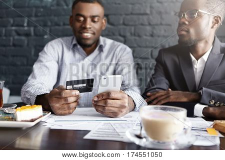Modern Technology And Online Payment. African Businessman Having Lunch With His Partner, Sitting At
