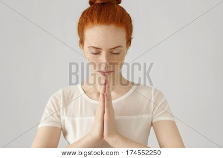 Young Redhead Woman Practising Yoga, Holding Hands In Namaste And Keeping Her Eyes Closed. Caucasian