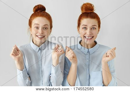 People, Emotions And Feelings. Two Attractive Happy Young Redhead Women With Hair Knots Wearing Ligh