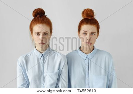 Human Face Expressions And Emotions. Portrait Of Two Cute Redhead Student Girls Wearing Same Hairsty