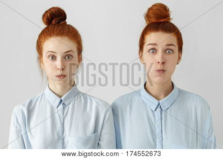 Two funny bug-eyed young European females with same hairstyles, dressed in identical shirts, blowing cheeks, having astonished amazed expressions on their faces. Human emotions and feelings