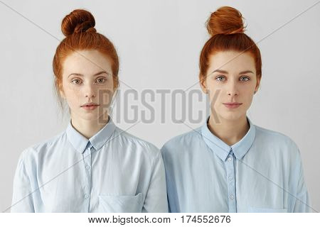 Indoor Shot Of Two Gorgeous Redhead Girls Looking Alike Wearing Same Hair Buns And Identical Shirts