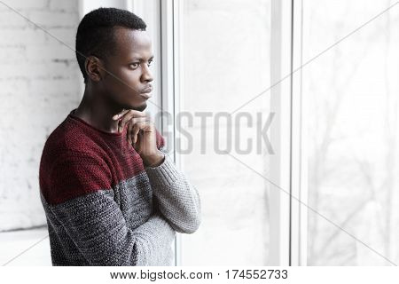 Indoor profile portrait of young African-American architect or designer wearing casual sweater standing at window looking out with thoughtful expression thinking of future waiting for inspiration