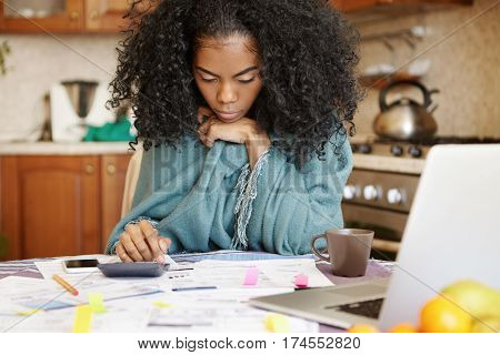 Single African-american Mother With Many Debts Feeling Stressed Calculating Finances, Siting At Kitc