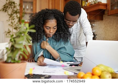 Young African Couple Facing Financial Stress: Woman In Wrap Holding Piece Of Paper, Reading Notifica