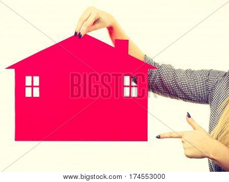 Female Hand Holding Red Paper House Symbol
