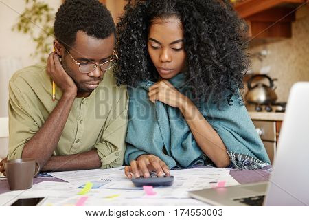 Candid Shot Of Stressed African Couple Reviewing Their Finances At Home: Woman And Her Husband In Gl