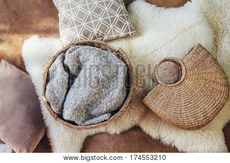 Wicker storage basket with woolen blanket inside, handbag and cushions on sheep carpet, top view from above. Natural and organic interior decor.