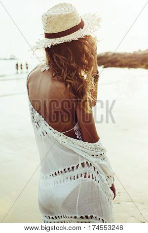 Beautiful boho styled model wearing white crochet swimsuit posing on the beach in sunlight