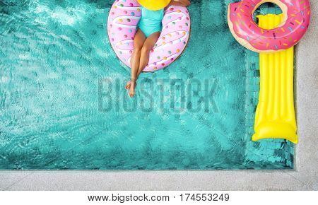 Woman relaxing on donut lilo in the poolside at private villa. Inflatable ring and mattress. Summer holiday idyllic. High view from above.