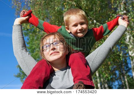 Happy boy sits on mother shoulders in the nature. Happy yuong mother and son at beautiful day.