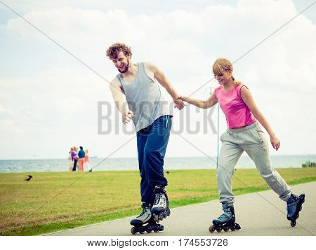 Active holidays exercises relationship concept. Young woman and man dressed up in sporty way holding their hands while rollerblading together on promenade.