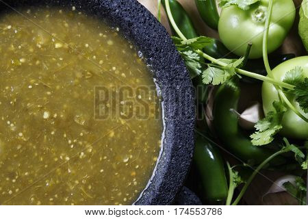 Stock image of mexican salsa verde on mortar and pestle with ingredients