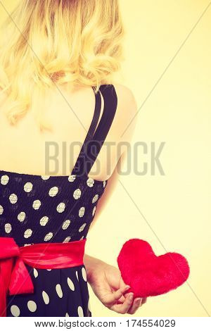 Valentine day gift proof of love romantic present concept. Woman in retro polka dot dress holding small furry red heart
