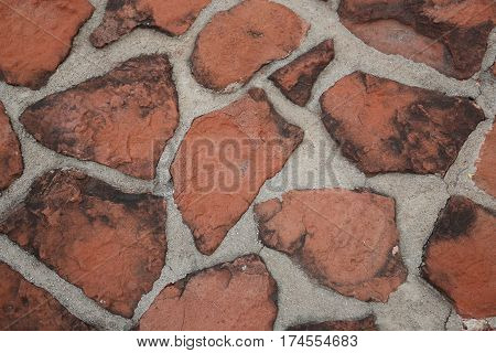 Path constructed of red flagstone-like rocks inlaid in cement, with blackened edges, possible background.