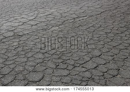 Crumbling asphalt-gravel roadway, showing its age and the effects of traffic and weather.
