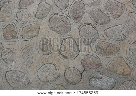 Looking down on a path or patio surface constructed of flat rocks inlaid in cement, with an incised line around each; could be background.