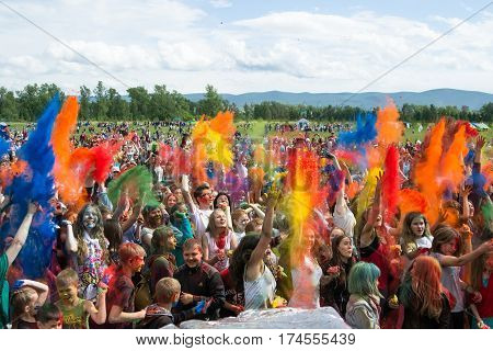 All participants simultaneously thrown in the air colored powders. KRASNOYARSK RUSSIA - JUNE 2015: People celebrate Holi-like part of festival Green