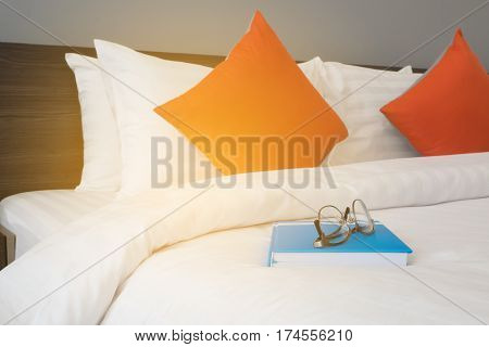 white bed with modern glasses on blue book at bed room.