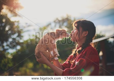 Silhouette Photo Of Young Woman With A Ponytail Giving A Kiss To Her Cute Little Brown Chihuahua Dog