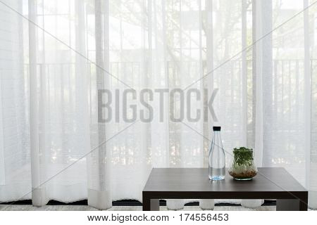office desk with bottle of water and garden plant on glass vase on white drape background texture at living room front view on table.