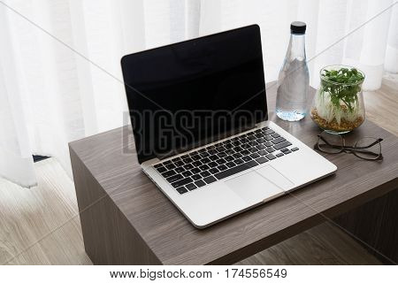 office table with blank screen on laptop bottle of water modern glasses garden plant on glass vase on white drape background texture. top view table.