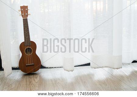wood ukulele on white drape background texture.