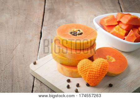 kitchen table with stack layer slice fresh papaya papaya and orange heart shape on cutting board - healthy eating and dieting food concept of health care.