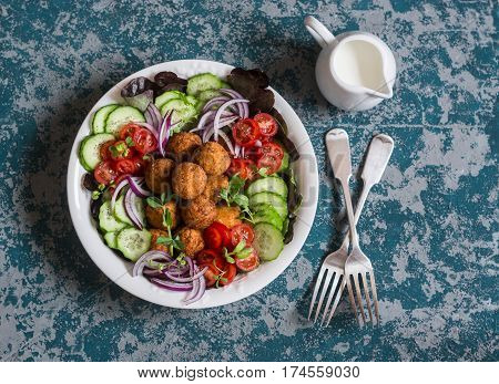 Falafel and vegetables salad. Delicious vegetarian food concept. Buddha bowl on dark background top view