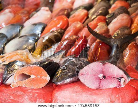 Salmon and tuna two of the world's most popular fish species with local fish in the background at a fish market in Manila The Philippines. Shallow depth of field with the tuna in focus.