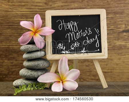 stack of pebbles and mini blackboard with text happy mother's day
