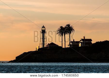 Silhouette of the new Point Loma lighthouse in San Diego, California with an orange sky.