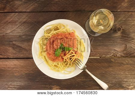 An overhead photo of a plate of spaghetti with a fresh homemade tomato sauce and a glass of white wine, with a place for text