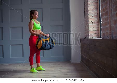 beautiful woman is holding a sandbag in the gym.