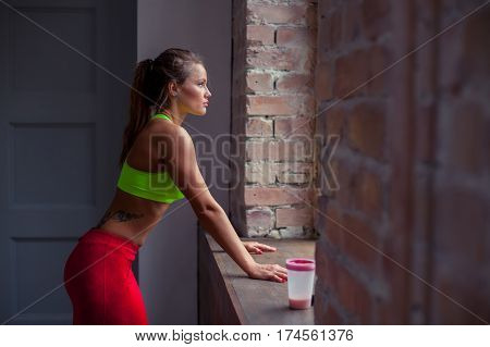 Good-looking fitness girl with tattoo in green top is standing in the gym nearby big windows, looking there and thinking. She is exhausted after training.