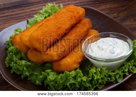 Plate of fish fingers remoulade sauce served on lettuce salad leaves