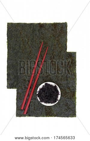 Nori japanese seaweed in sheets with dried hijiki in a white porcelain bowl and red chopsticks on white background with copy space.