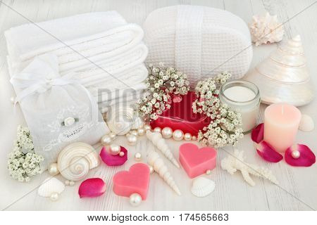 Bathroom spa products with soap, moisturising cream, towelling accessories, gypsophilla flowers, shells and pearls on distressed white wood background.