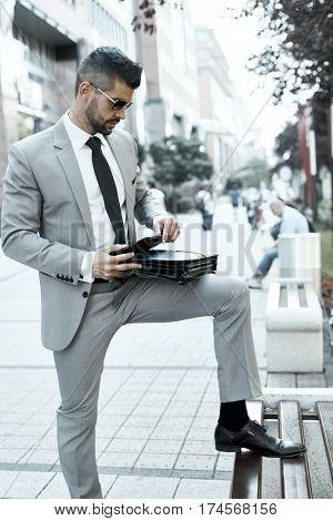 Portrait of young elegant businessman on city street holding suitcase.
