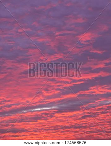 blue magenta and red sky at sundown with heavy clouds
