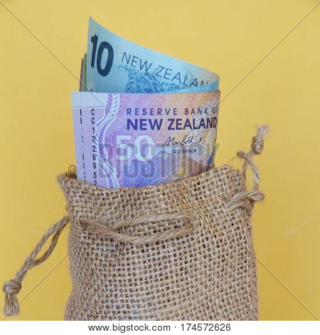 New Zealand dollar notes in a brown hessian sack (square)