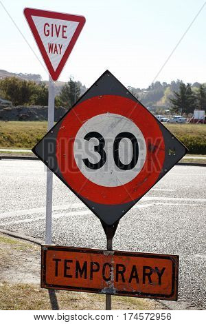 Temporary speed restriction road works sign showing 30 kilometres per hour limit used in New Zealand and Australia
