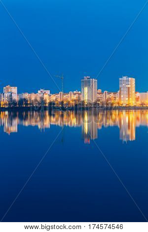 Night View Of Urban Residential Area Overlooks To City Lake Or River And Park In Evening Illumination, Reflecting In Water Surface. City Residential Area Architecture