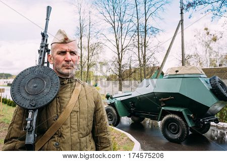 Pribor, Belarus - April 23, 2016: Unidentified Re-enactor Dressed As Russian Soviet Infantry Soldier Machine-gunner Of World War II Standing At Armoured Soviet Scout Car BA-64
